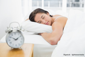 Young woman sleeping in bed with blurred alarm clock on bedside